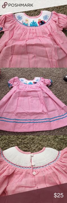 "❄️""Ice Princess"" Frozen smocked bishop dress ""Ice Princess"" collection. Pink gingham and blue trim along bottom. Smocking all around neck on both sides, bishop sleeves and button up back. Anna and Elsa smocked on the front. Only TWO left! *26 12m-- chest 12""; length 19"". 18m-- chest 13""; length from scoop of neck to hem 20"". No offers please due to our items already being priced lower than regular store price and Poshmark fees. Select buy now or add to bundle :) NOLA Smocked Dresses Casual"