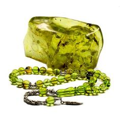 Caribbean Green Amber. Large piece with clearly visible insect inclusions. In the foreground are prayer beads. Fosilli Özel Yeşil Damla Kehribar Tesbih