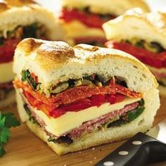 Italian Stuffed Sandwich Wedges Recipe Lunch and Snacks with italian bread, crisco, pimento stuffed olives, black olives, flat leaf parsley, dried oregano, pepper, crushed red pepper flakes, lemon juice, minced garlic, salami, mozzarella cheese, roast red peppers, drain, pepperoni slices