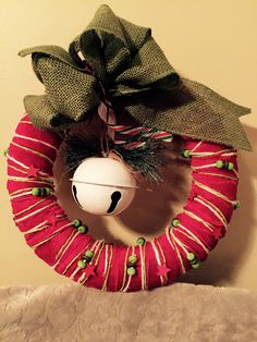 "10"" wreath covered with strips of red velvet and twine garland with red and green stars and balls.  White metal bell, green burlap bow."