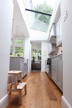 Lots of light in this kitchen.  Grey cabinets (white uppers?), wood floors.