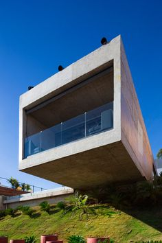 Cantilevered concrete box houses poolside bar at weekend retreat in Belo Horizonte.
