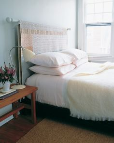 Quilt Headboard, from Martha Stewart.  Purchase a wooden drapery rod, two brackets, and hanging hardware from a home-supply store. Paint the drapery rod and brackets to match the bedroom walls, and let dry. Install the brackets above the bed, positioning them at the desired height, and put the rod in place. Drape the quilt over the rod, lining up the bottom edges so that it hangs evenly.