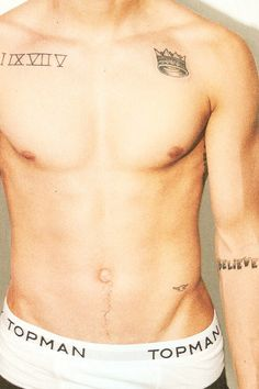 Justin Bieber's Believe tatto on his left arm and the crown on his left shoulder. The roman numeral's for 1975 is on his right shoulder