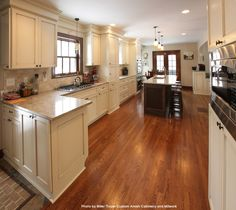 Traditional kitchen with plenty of space, a dark wood breakfast bar with bar stools, white kitchen cabinets, remodeled hardwood floors and a large range in front of the window. Gorgeous. #ktichens