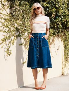 Midi | Button-down denim midi skirt with a flattering A-line silhouette and four-pocket design. Deep apron-style front pockets and a raw hem complete the look.