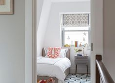 White Bedroom with Patterned Cushion and Rug