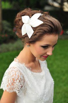 Tiara Melissa, para penteados de cabelo preso ou solto, tem aplique de um lírio feito em cetim. Brinco Isabel G, de prata com um ponto de luz de zirconia no centro.