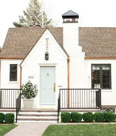 "White Brick Tudor House and Front Door in Benjamin Moore's ""China White"" and ""Greyhound"""