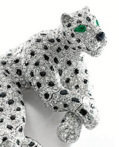 PLATINUM, DIAMOND, ONYX AND EMERALD PANTHER BROOCH, CARTIER, PARIS Designed as a panther in repose with an articulated tail and paws and a head that swivels, set with round diamonds weighing 17.42 carats, accented by an onyx nose and spots, further decorated with two pear-shaped emerald eyes weighing .20 carat