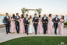 San diego beach wedding at admiral kidd club bride mermaid style lace gown with straps and low back design with sweetheart neckline and medium lace veil with groom charcoal grey tuxedo with black lapel and white dress shirt with black bow tie and black vest with white floral boutonniere walking with bridesmaids long pink dresses and groomsmen charcoal grey suits with blush pink bow ties
