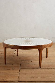 I would try out the round table you have in their now as a coffee table first.  If you like that shape, but not necessarily the look your house could totally rock this.