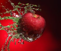 Apple in juice. Red apple in juice stream ,