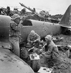 Americans take a meal break near wreckage of aircraft during a lull in the fighting on Iwo Jima, 1945.