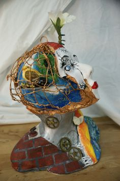 """""""Who I Am"""" a mixed media sculpture By: HollyAnne Black. Gears, flowers, bird, abstract, caged bird, fire hair, shattered countenance, broken china doll"""