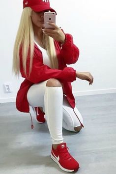 a blond teen girl taking a selfie in a mirror A tomboy street style look with White Jeans and Red Nike Sneakers and a Red Jacket