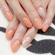 Peach nails with gold studs and an accent finger.