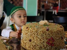 A young boy in a traditional outfit is protective of his Chak-Chak, a traditional Tatar dessert made of wheat and honey. Radio Azatliq/Firuza Absalamova.