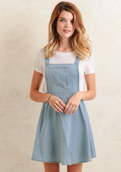 We absolutely adore this darling overall-style dress crafted in a light-blue chambray design with beige stitch accents. It features a large front pocket at the bust, a flared skater-style skirt...