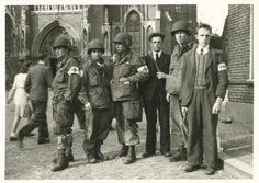 Vier Amerikaanse gewondenverzorgers en een tweetal verzetsmensen van de Landelijke Knokploegen Oranje tijdens zuiveringen in Veghel, direct na de bevrijding.