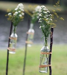 italian glass water bottles with large twigs and a native sprig of a plant in each to line the processional and recessional route.