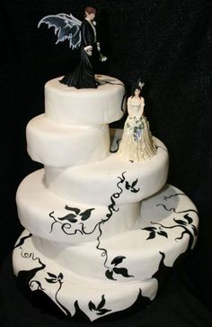 gothic wedding cake Gothic theme six tier black and white Gothic style wedding cake. The round tiers are off centre making it a very unique cake indeed. Hand painted with black decorations. Gorgeous bride and groom gothic wedding cake topper. The groom cake topper has wings and is dressed in black, while the bride is dressed in ivory, holding a lovely bridal bouquet. By LusciousCreations
