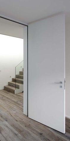 Stumpfe massive Räuchereichen-Rahmentüren mit weißem Holzfutter.