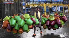 Vendedor carrega jarros de água em um mercado na cidade indiana de Bangalore