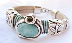 """Lovely embossed Regaliz leather in subtle nude blends with a lovely silver plated swirl surrounding a turquoise bead sandwiched between metallic turquoise leather and silver leaf beads. Fits 6 1/2"""" wrist. http://www.etsy.com/shop/Vynyard"""