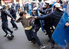台湾・台北(Taipei)の行政院(内閣)庁舎前で、警察官ともみ合いになるサービス貿易協定に反対するデモの参加者(2014年3月24日撮影)。(c)AFP/SAM YEH ▼25Mar2014AFP|【写真特集】台湾警察、対中協定反対派を強制排除 http://www.afpbb.com/articles/-/3010935
