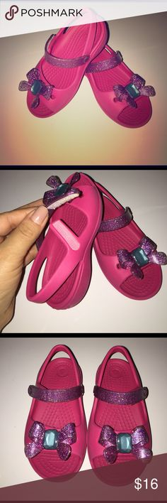 CROCS fit for any little princess! Pink CROCS with purple and teal glittery bow in C8. Slightly used and in great condition! CROCS Shoes Sandals & Flip Flops