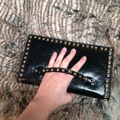 """Last one!!! Black studded clutch with hand strap Beautiful faux leather studded clutch, with hand strap. Magnetic snap closure. Three main pockets, two small cell phone pockets, one internal zippered pocket, one external zippered pocket. Height: 6.25"""", width: 11"""", height when open: 13"""". Wristlet and on the shoulder option. Several colors available. Brand new from vendor, NO TAGS. In original packaging. Bags Clutches & Wristlets"""