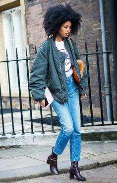 Julia Sarr Jamois wears a graphic t-shirt, bomber jacket, jeans, and Louis Vuitton monogram boots
