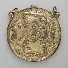 Valve of a Mirror Case Date: 1180–1200 Culture: British Medium: Bronze gilt Dimensions: Overall: 3/8 x 4 3/8 in. (0.9 x 11.1 cm) The only known surviving element from a Romanesque mirror case, this valve was originally slotted and joined by a clasp to a matching one. Mirrors of polished silver were fitted into the inner facings.  foliate lugs and attached rings are modern additions.