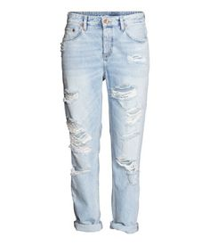 5-pocket, low-rise jeans in washed denim with heavily distressed details, a button fly, and tapered legs.