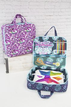 """This bag features ample storage space for any project or hobby - quilting, drawing, hand-sewing, and so much more! The lining features a zippered pouch, mesh zippered pocket, and elastics for holding pens or other items. The bottom of the case has an elastic buckle strap to hold quilt blocks, books, and rulers. Click here to read more details about this sewing pattern, and to see photos of all the tester bags! Finished Size: 14"""" long x 13"""" high x 3"""" deep (35.5cm x 33cm x 7.5cm) The pdf…"""