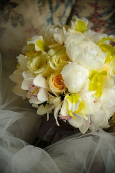 Lovely white and yellow bridal bouquet made of yellow roses, white peonies and orchids.
