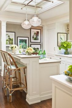 There's a warm and inviting feeling in this kitchen. The bar chairs have backs that come above the raised eating counter top, and a charming style. @Barbara Wirth Art really likes the framed paintings or pictures hung on the wall. They add real personality to the whole room!