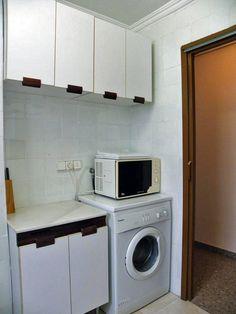 Cocina equipada, con lavadora, microondas y mobiliario.
