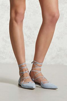 A pair of faux suede d'Orsay flats featuring a pointed toe, lace-up top, and a low stacked heel.