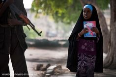 A girl, clutching a notebook, passes an armed man, on a street in Mogadishu, the capital of Somalia. There are twenty-eight million children out of school in conflict countries, that is larger than the population of Australia. UNICEF/Kate Holt