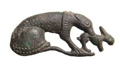 Romano-British bronze brooch depicting a hound holding a rabbit in its mouth, c. 2nd Century AD, nicely detailed and lacking the pin and catch. L: 1 2/5 in (3.6cm).