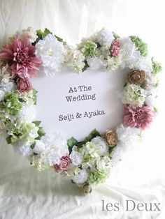 お花の枠でウエルカムボードを華やかに バラやダリア、シャクヤクなどのアーティフィシャルフラワーをハート形に飾って。中央にふたりの名前やメッセージをあしらって♪吊るしても可愛いですよ。