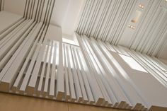 Undulating acoustically treated wood panels and strips of acoustical material can be arranged to create random sound diffusion and add to the visual experience of rooms as well.