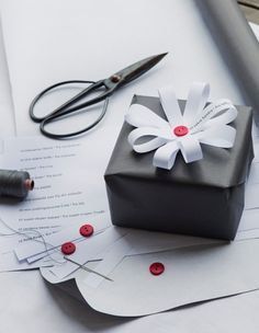 (A través de CASA REINAL) >>>>  Print out the gift tags and cut the text into strips. Gather the strips in the middle with a sewn button. Attach the rosette on the package with a double-sided tape.