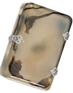 AN ART DECO AGATE AND DIAMOND CIGARETTE CASE, 1920. The rectangular agate case accented to the hinges and clasp with millegrain-set rose-cut diamonds, measurements approximately 86 x 56 x 13 mm.