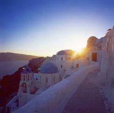 High-Res Stock Photography: Greece Cyclades Santorini sun setting behind buildings…