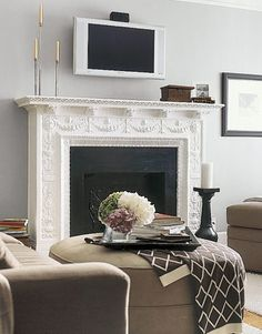 Like many apartment fireplaces, this one is strictly decorative. Placing a TV and stereo unit above the mantel turns the hearth into a functional focal point (no need for a bulky armoire).
