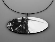 """Julia Turner """"Border"""" pendant, 2010. Wood, paint, steel, silver. 1.5 x 3.5 x .5 in (3.8 x 8.9 x 1.3 cm)."""