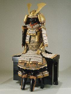 黒漆塗揺ぎ札白綾威鎧 くろうるしぬりゆるぎざねしろあやおどしよろい  日本 江戸時代後期 鉄製漆塗、革、絹 1 漆塗りの仕上げと威しの手法が優れており、揺ぎ札の流行した江戸時代後期の希少な逸品である。兜をはじめ、鎧の各部に牡丹模様の金物が、また胴の前面には尾長島の藍染抜きの模様が施されている。全体に落ち着いた調子に統一され、極めて美しい鎧の一つである。